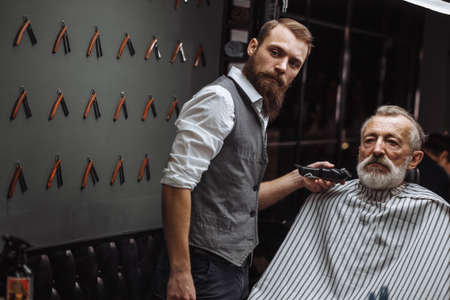 Professional hairdresser doing beard design, trimming hairs with electric razor. Beauty salon. Male beauty. The client is a mature respectable gentleman.