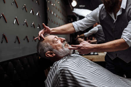 Respectable senior caucasian man visiting hairstylist in barber shop for shaving and making new design for his grey-haired beard