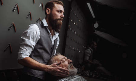 Male stylish barber choosing the hair style for his mature old aged client with grey beard and moustache, looking at the mirror.