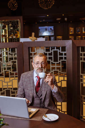 Senior european businessman in three piece suit having lunch at restaurant, drinking coffee, reading latest news from newspaper, taking no break from business.