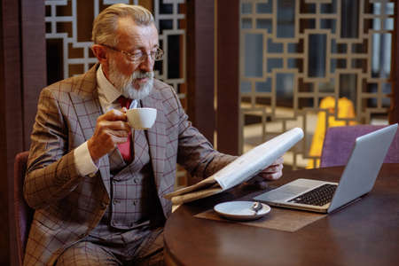 Senior european businessman in three piece suit having lunch at restaurant, drinking coffee, reading latest news from newspaper, taking no break from business. Stock fotó
