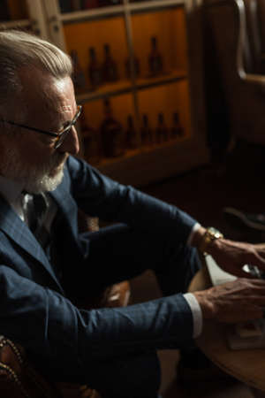 Handsome old male pensioner dressed in smart formal style using laptop and smoking while sitting on couch at luxury home interior with cabinet with expensive alcohol.