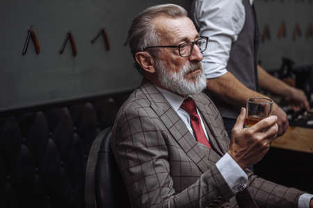 Bearded elderly businessman in stylish expensive suit drinking whiskey while getting a haircut by the barber in the barber shop
