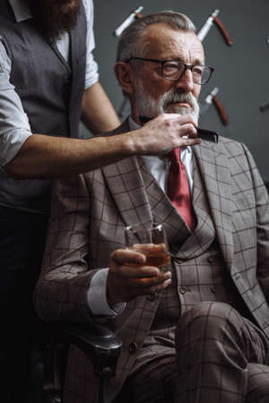 Barber making male haircut. Hairdresser cutting hair of his rich client, dressed in expensive stylish man s suit of clothes and holding a glass of alcoholic beverage