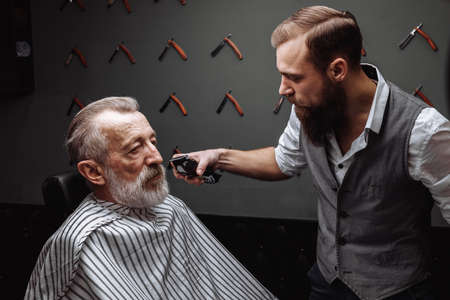 Close up of a hairdresser s work for a handsome respectable old-aged bearded man at the barber shop. He is doing styling with the electric shaver.