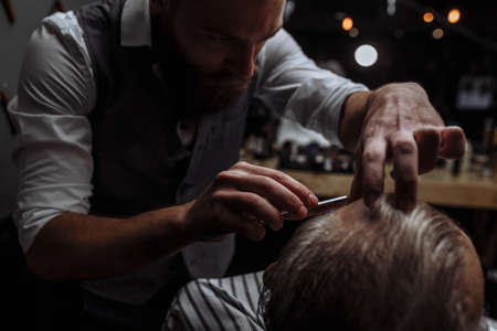 Caucasin old man getting his beard shaved by barber visiting hairtician at shaving saloon, close up