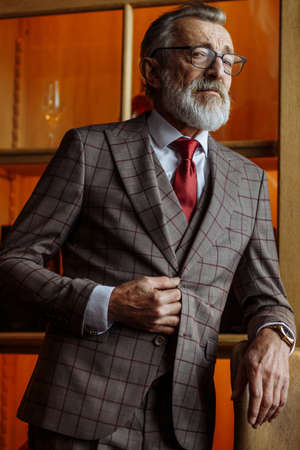 Portrait of whitebeard male with short grey haircut, dressed in tailored formal mens clothing posing with thoughtful look at luxury office interior, making serious business decision Archivio Fotografico