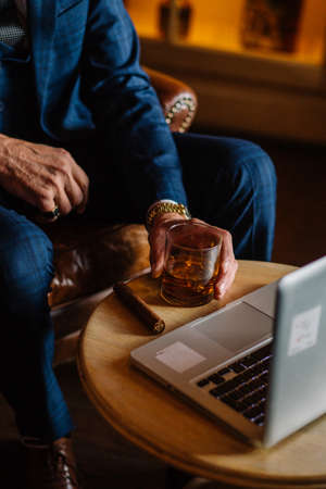 Bearded old-aged playwriter looking at laptop and wrting his new novel while sitting in restaurant at night. To help his creative impulse flow he smoking a cigar and sipping whiskey