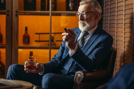 Elegantly looking aged grey-haired chief of big company relaxing at restaurant smoking cigar and carrying glass of whiskey while gazing at the screen of laptop and spending time till night sleep.