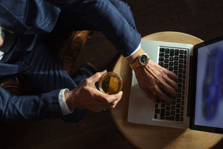 Old man s hands in stylish dark blue suit working on laptop while relaxing at restaurant while carrying glass of wisky, top view