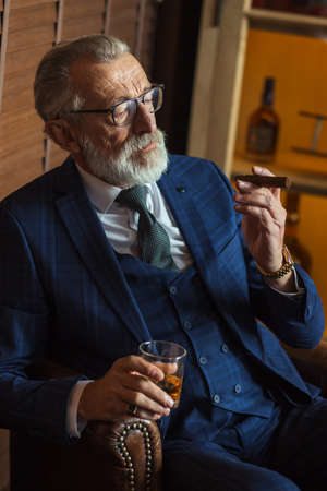Senior cute business man with cigar and whisky. Gray hair and beard wearing blue tailored suit and tie, relaxing at fashionable restaurant lounge