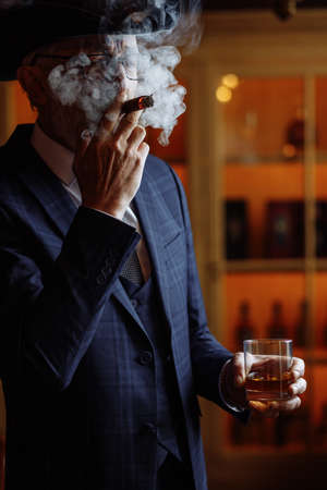Concept of old age, wealth, prosperity and experience. Prosperious confident aged man with grey beard and spectacles, wearing big dandy hat smoking cigar and sipping cognac in luxury interior