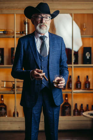 Portrait of old-aged male dandy dressed in elegant trendy men s suit in big hat smokes cigar and drinks alcoholic beverage.