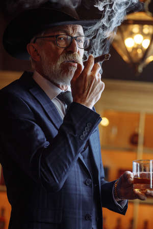 Big boss in retro style. Serious senior man in wide-brimmed hat and tailored suit, smoking cigar and looking at you while standing against pub interior.
