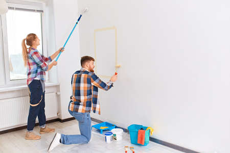 Team of two professional male and female young painters in checkered wear with brushes and rollers working indoors, making wall colour renovation of the house.