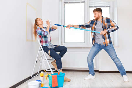 Team of professional painters in checkered wear with brushes and rollers working indoors