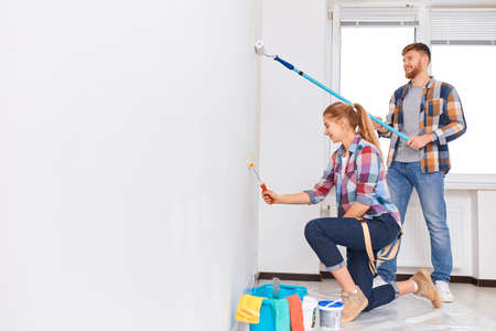 Couple in casual plaid shirts painting house wall together, side view. Painted walls today, despite the huge variety of finishing materials, are very popular.