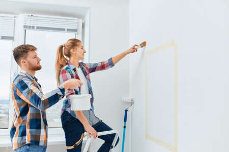 Happy girl in casual plaid shirt painting white house wall with brush and her boyfriend helps her, holding the paint bucket near her hand