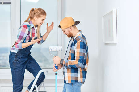 Young woman sharing her interior design ideas, standing on a ladder while her boyfriend listen to her holding paint roller with a hand stick in empty white appartment.