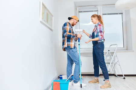 Newlyweds quarrelling because of renovation in new apartment. Pissed off irritated young woman scolding her embarrassed guilty partner standing in white room with set of paint tools 版權商用圖片