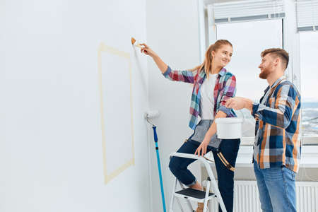 Young couple started a painting company, and as a favor to their landlord, they came over and started painting his new office. 写真素材