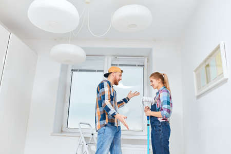 People, renovation concept - Young woman and man discussing colour of paint for walls standing in empty white room