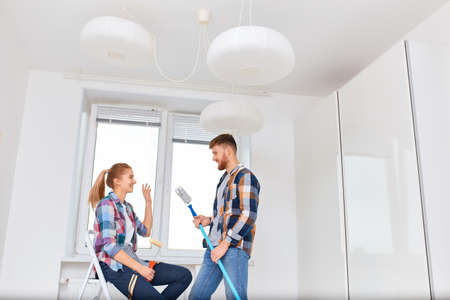 Happy smiling young couple planning new apartment interior design, while making renovation sitting on ladder with the set of paint tools in empty white appartment. Banco de Imagens