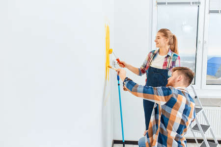 Creative young couple in casual plaid shirts painting a heart sign with yellow colour decorating their bedroom in rented house.