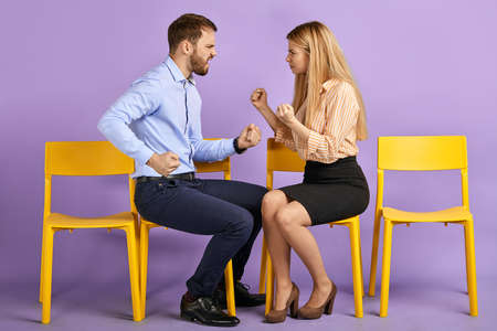 young male with fists up and laughing female students joking and playing fist-fighting, having fun and waiting for job interview