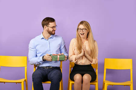 pretty young blonde woman gets unexpected present from her male friend and waiting for job interview Foto de archivo