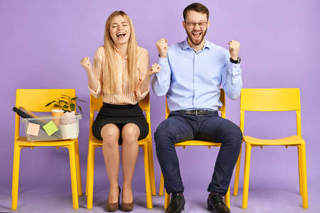 happy young blonde woman with closed eyes and man in round eyewear sitting extremely excited by great news and waiting for job interview Foto de archivo