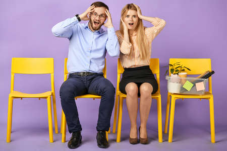 excited and shocked young man in round eyewear and blonde woman received unbelievable news, sitting and touching heads and waiting for job interview