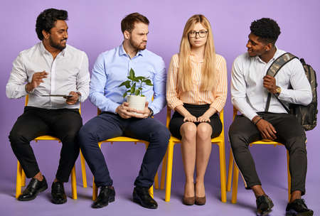 multinational team sitting together and looking at pretty girl in glasses. Young man with house plant looking jealous waiting for job interview