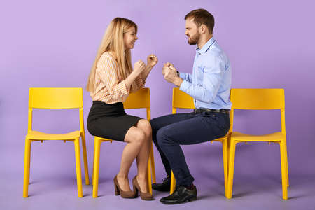 young male with fists up and laughing female coworkers joking and playing fist-fighting, having fun. Looking at each other and waiting for job interview