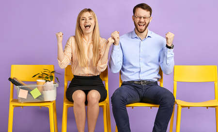 happy young blonde woman and man in round eyewear extremely excited by great news sitting on chairs on white background and waiting for job interview