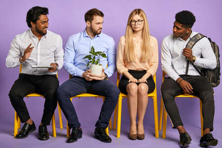 multinational coworkers looking at pretty blonde girl in glasses waiting for job interview