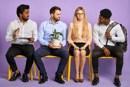 multiethnic men flirting with young pretty blonde woman in glasses waiting for job interview