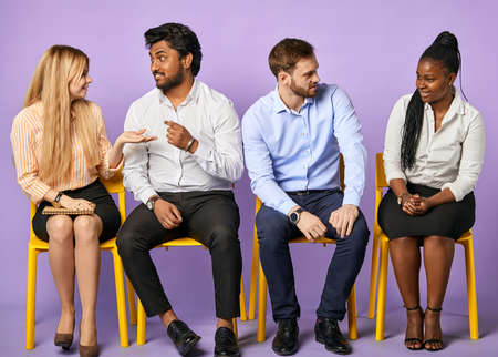 group of young multinational people sitting and having discussion and waiting for job interview