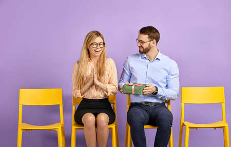 pretty young woman in glasses surprised by unexpected present from her male friend and waiting for job interview Foto de archivo