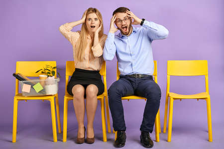 excited and shocked young man in round eyewear and blonde girl received unbelievable news, sitting and touching heads and waiting for job interview