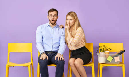 pretty blonde young woman holding finger on lips showing asking to keep the secret, young man in glasses amazed and shocked and waiting for job interview