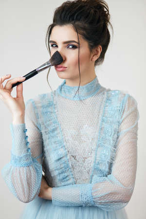 beautiful lady powdering her nose, close up photo. isolated white background, studio shot 版權商用圖片 - 153257039