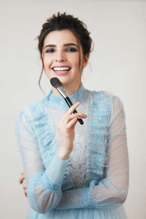 laughing girl with a brush looking at the camera. cosmetic procedure, happiness 版權商用圖片 - 153257040
