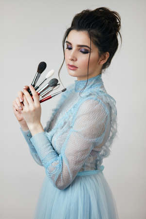 attractive girl choosing a brush to finish her makeup, close up photo. pensive girl looking at the brushes for face, face care 版權商用圖片