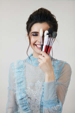 funny shy girl closing her one eyes with brushed for makeup, close up photo. happiness concept, emotion, feeling, a good, complete set of brushes 版權商用圖片 - 153257055