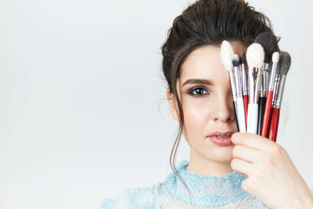 Beautiful woman with makeup brushes near her face, copy space.the secret of beauty, makeup collection 版權商用圖片 - 153257057