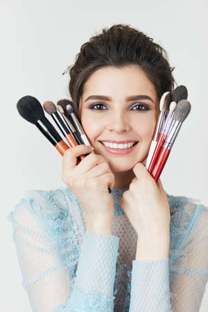 charming beautiful gorl holding a set of brushes, close up photo. positisve girl likes stylish makeup, different types of makeup brushes 版權商用圖片 - 153257058