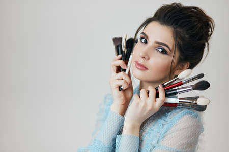 job, profession, interest, lifestyle, close up photo, copy space, lovely girl holding cosmetology tools near her perfect face, choose any brush you like 版權商用圖片