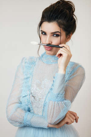 funny girl using a brush like a moustache, close up photo, studio shot, crazy pretty girl having fun with a cosmetic