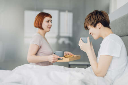 pleasant girl brings hot green tea for a girlfriend. close up photo. weekend, holiday Zdjęcie Seryjne